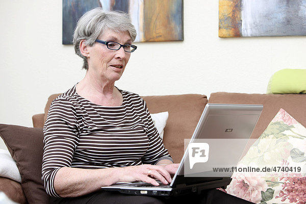 Woman  about 65 years old  at home  surfing the Internet on a laptop