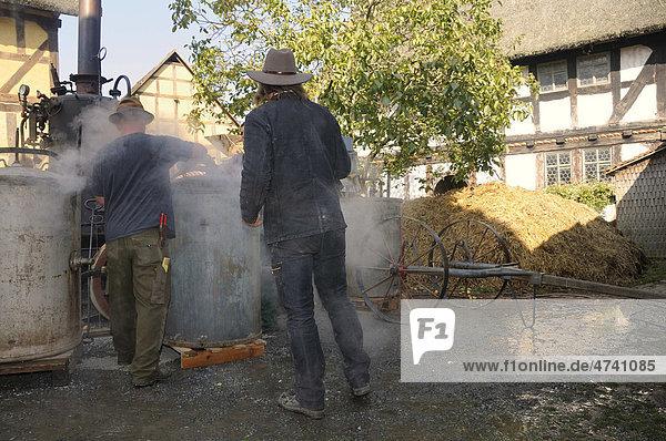 Men steaming potatoes in a potatoe-steamer  Hessenpark outdoor museum near Neu-Anspach  Hochtaunuskreis district  Hesse  Germany  Europe