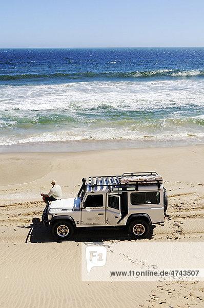Mann mit Geländewagen Landrover Defender am Strand des Atlantischer Ozean  Namib Naukluft Nationalpark  Teil des Namib-Skelettküste Nationalparks  Skeleton Coast  Wüste Namib  Namibia  Afrika