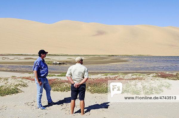 Männer im Feuchtgebiet Sandwich Harbour  Namib Naukluft Nationalpark  Teil des Namib-Skelettküste Nationalparks  Skeleton Coast  Wüste Namib  Namibia  Afrika