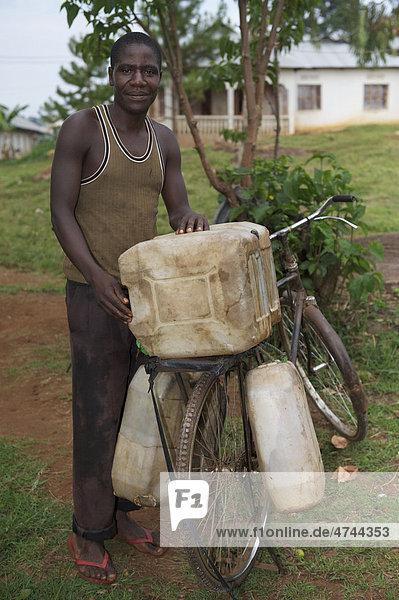 Mann beim Wasserholen mit dem Fahrrad in einem Dorf in der Nähe von Bukoba  Tansania  Afrika