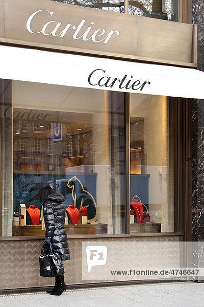 Woman looking at the display in the shopwindow of the Cartier jewelry store  Koenigsallee shopping promenade  short Koe  Duesseldorf  North Rhine-Westphalia  Germany  Europe