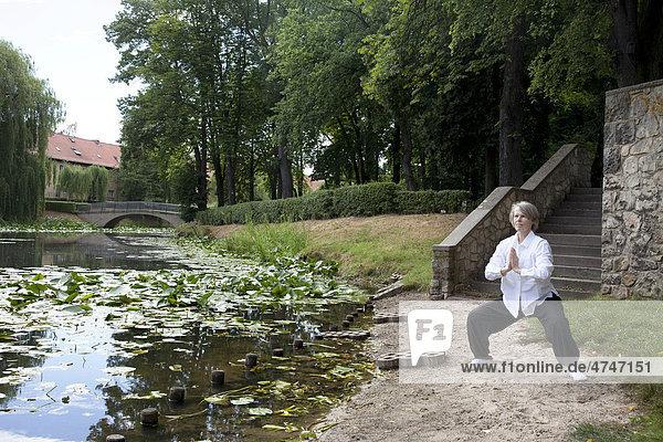 Anna Elisa Heine in einer Qi Gong Übung  Nei Yang Gong  Innen Nährendes Qigong im Lindenhof  Lindenhof-Weiher mit Seerosen  Schöneberg  Berlin  Deutschland  Europa