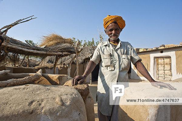 Ein freundlicher älterer Mann mit Turban steht an seiner Grundstücksmauer  Wüste Thar  Rajasthan  Indien  Asien