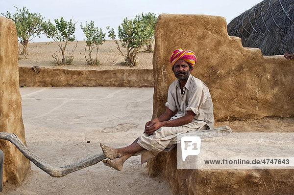 Ein Inder  mit Dhoti und Turban bekleidet  sitzt vor seinem Hofeingang  die Beine lässig über einen Holzknüppel gelegt  Wüste Thar  Rajasthan  Indien  Asien