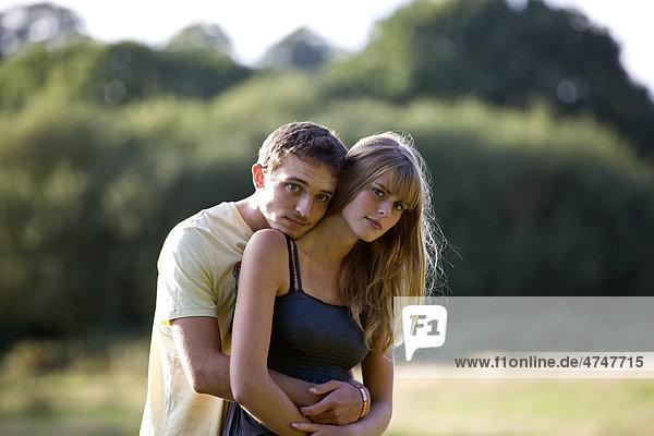 Ein junges Paar steht im Freien  umarmen