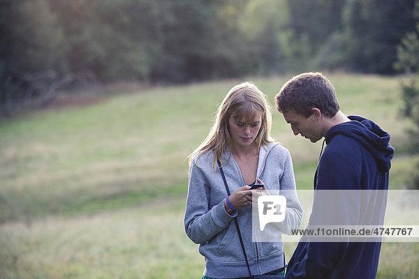 Junges Paar im Freien  eine Frau mit einem Mobiltelefon