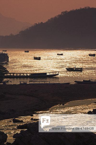 A sunset scene over the Mekong river where it meets the Nam Khan river  Luang Prabang  Laos  Southeast Asia