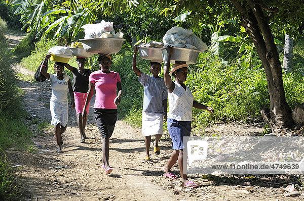 Frauen mit Wäsche auf dem Kopf auf dem Weg zur Quelle zum Waschen  Dorf Charle Magne in den Bergen bei Petit Goave  Haiti  Karibik  Zentralamerika