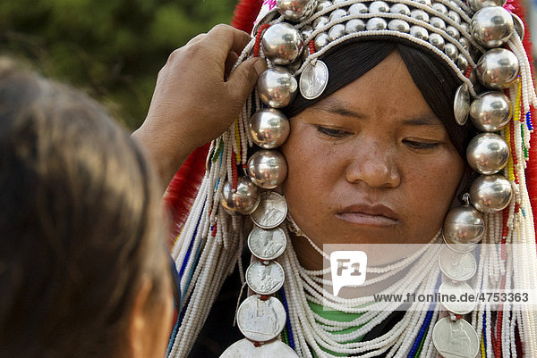 Akha hill tribe woman getting dressed in her traditional costume in Mae Salong  north Thailand  Asia