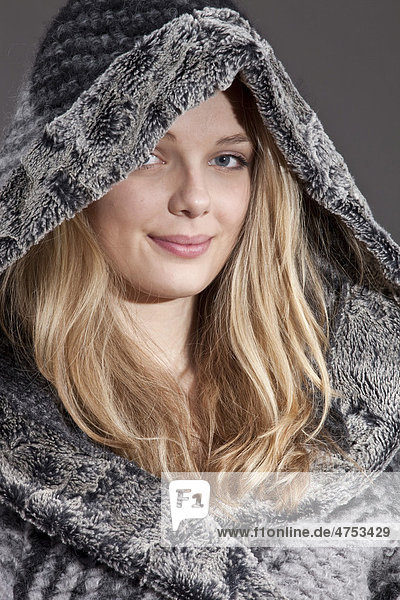 Smiling young woman in a hooded winter jacket