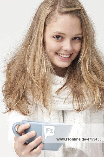 Blonde  weißgekleidete junge Frau  mit hellblauer Teetasse