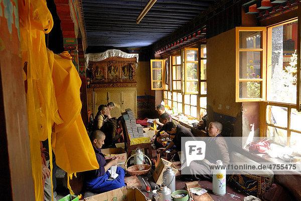 Tibetische Nonnen sitzen im Nonnenkloster Ani Tsakum  Ani Tsakung  bei der Arbeit und Herstellung der Texte zur Füllung tibetischer Gebetsmühlen  Gebetszylinder  Lhasa  Tibet  China  Asien