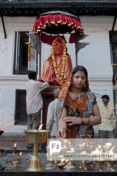 Hinduismus  Gläubige mit Butterlampen  Hanuman Statue  Platz vor dem Hanuman Dhoka Königspalast  auf dem Königsplatz Durbar Square  Kathmandu  Kathmandutal  Himalaja  Nepal  Asien