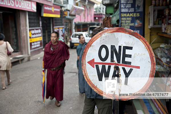 Monk walking in a street next to a one way traffic sign  Tibetan Buddhism  road in Upper Dharamsala  McLeod Ganj  Himachal Pradesh  India  South Asia  Asia