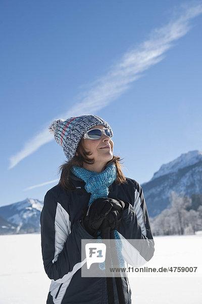Lächelnde Frau mit Nordic Walking-Stöcken in Winterlandschaft  Tannheimer Tal  Tirol  Österreich