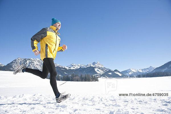 Mann joggt im Schnee  Tannheimer Tal  Tirol  Österreich