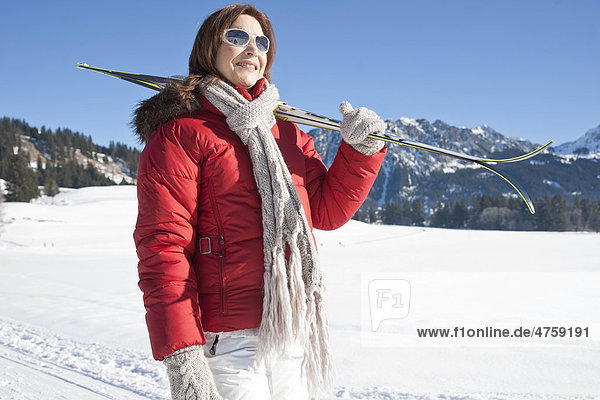 Frau mit Skiern in Winterlandschaft  Tannheimer Tal  Tirol  Österreich Frau mit Skiern in Winterlandschaft, Tannheimer Tal, Tirol, Österreich