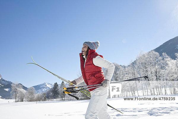 Lachende Frau mit Skiern in Winterlandschaft  Tannheimer Tal  Tirol  Österreich
