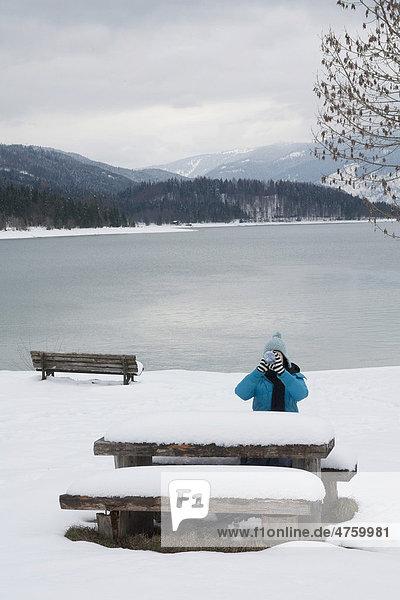 Frau trinkt aus einer Flasche am Walchensee  Picknicktisch  Winter  Bayern  Deutschland  Europa