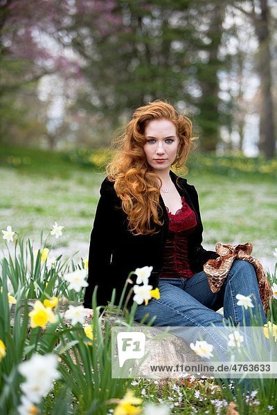 Portrait of a 28 year old redheaded woman in a field of daffodils
