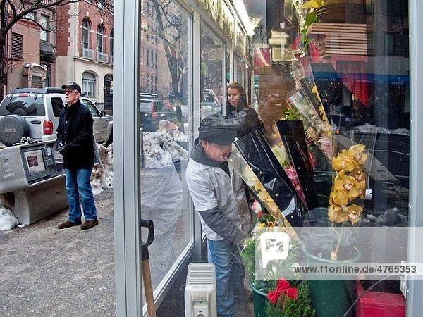 While her husband searchers for a taxi  a woman purchases fresh flowers at a warmed sidewalk kiosk on a winter day in New York City Note snow in street