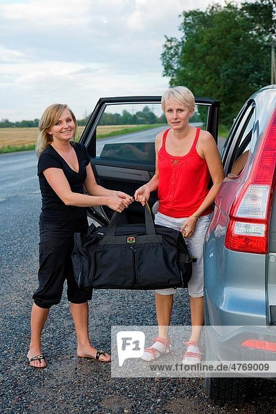 Two Happy Smiling Young Women Holding Nylon Sport Travel Bag by Car