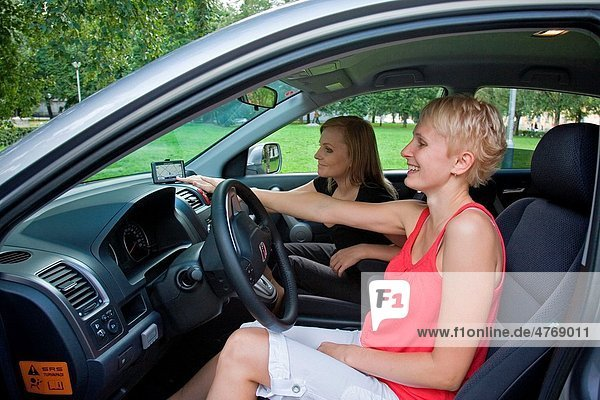 Young women in car on road trip using gps