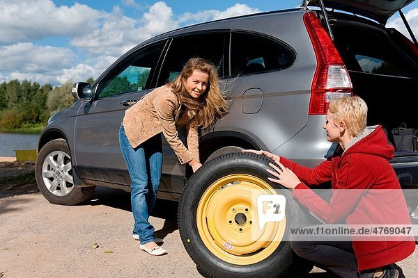 Two young women changing flat spare car tire