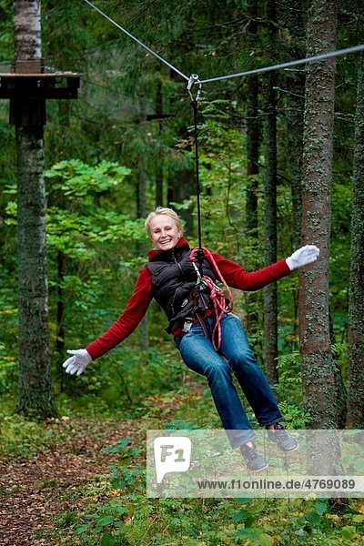 Young happy smiling woman driving on zip wire in adventure park trail in Otepää  Estonia
