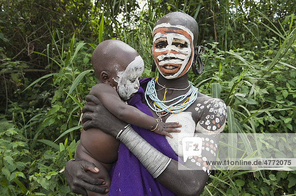 Surma woman with facial and body painting  holding her baby  Kibish  Omo River Valley  Ethiopia  Africa