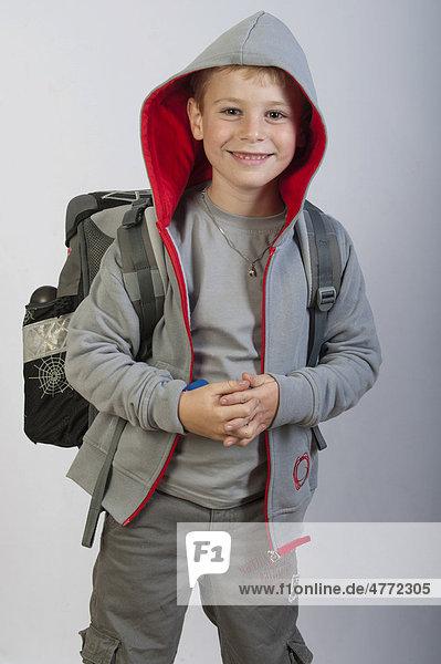 6jähriger Junge mit Kapuzenpulli und Schulranzen  Erstklässler  Schulkind