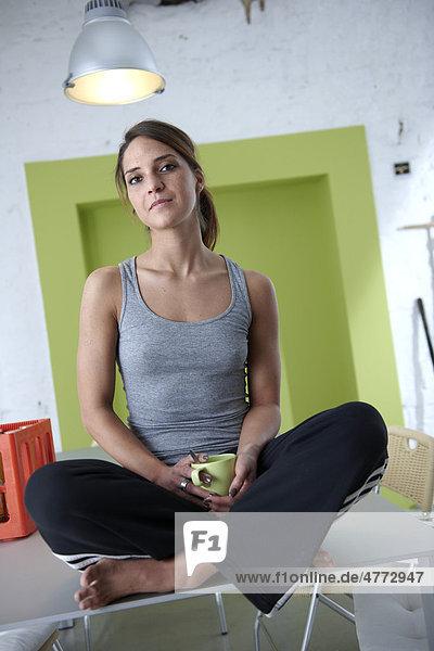 Junge Frau sitzt im Schneidersitz auf Tisch