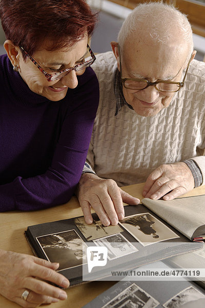 Alter Mann  Senior  92 Jahre  und Tochter  schauen sich ein Familienalbum an
