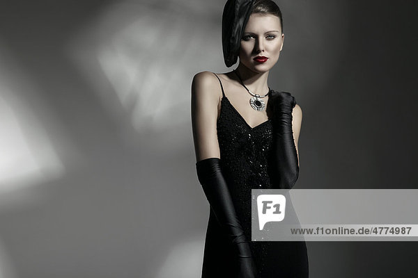 Junge Frau mit eleganter Mütze und schwarzem Kleid