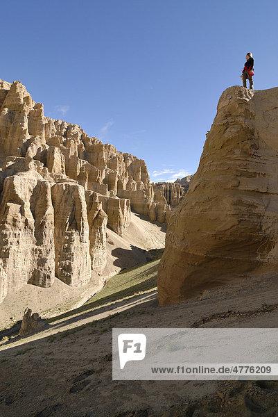 Frau steht auf Sandsteinfelsen in trockener Landschaft im alten Königreich Guge  Sutley Canyon  Westtibet  Provinz Ngari  Tibet  China  Asien