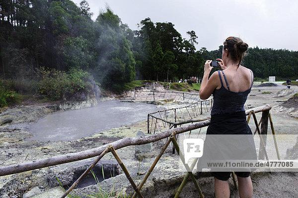 Frau fotografiert Fumarolen am Lagoa das Furnas auf der Insel Sao Miguel  Azoren  Portugal