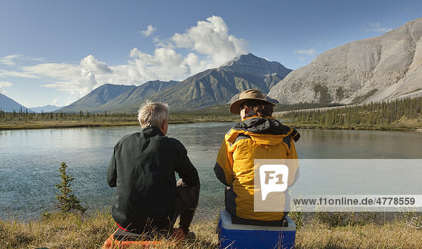 Paar  Mann und Frau sitzen am Ufer und genießen den Blick über den Fluss  Wind River Valley  nördliche Mackenzie Mountains Gebirgskette  Yukon Territorium  Kanada