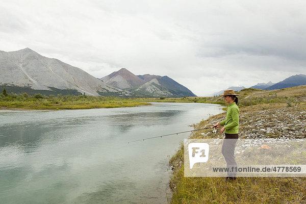 Junge Frau beim Angeln am Wind River  Mackenzie Mountains  Yukon Territory  Kanada