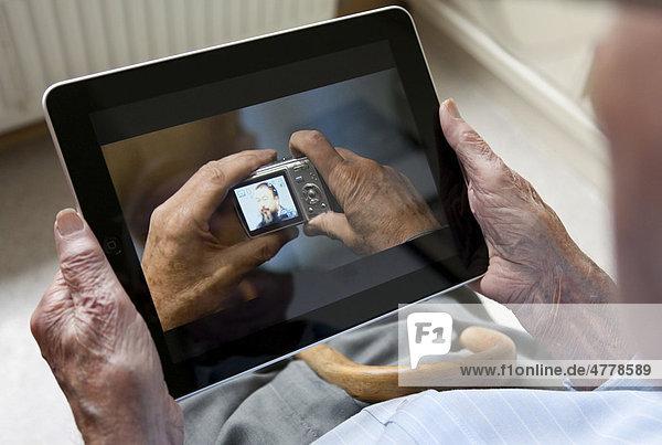 Senior betrachtet Foto vom chinesischen Künstler Ai Weiwei auf seinem iPad  Nahaufnahme Hände