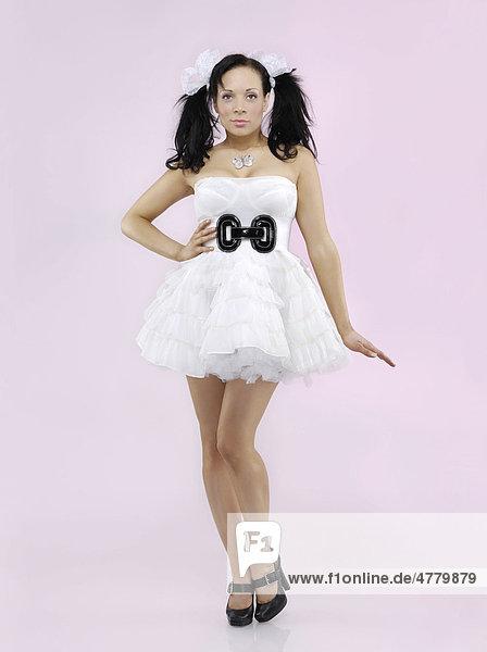 Puppenhafte Frau trägt ein weisses Kleid
