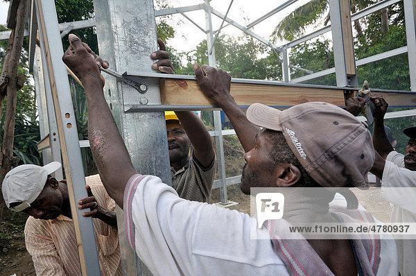 Reconstruction programme by an international aid organisation  victims of the January 2010 earthquake receiving earthquake-proof prefab houses  Palmiste-a-Vin near Leogane  Haiti  Caribbean  Central America