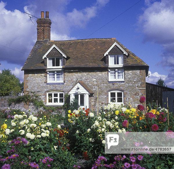 Cottage  Landhaus  aus Steinen gebaut  mit hübschen Dahlien im Vorgarten