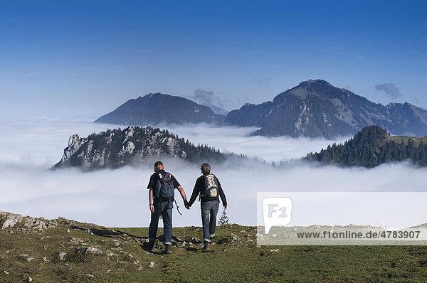 Wanderer Hand in Hand am Berg  schauen über Hochnebel zu Berggipfeln der Chiemgauer Alpen  Oberbayern  Bayern  Deutschland  Europa