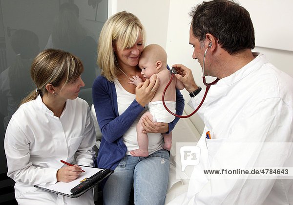 Doctor's surgery  mother and child at the paediatrician's  medical examination of an infant  preventive medical examination  doctor listening to the baby's chest with a stethoscope  preventive checkup