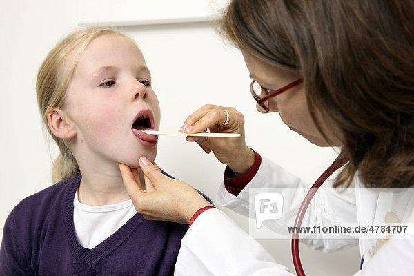 Arztpraxis  Ärztin und Mädchen  10 Jahre  bei einer Untersuchung  Kontrolle des Rachenraums
