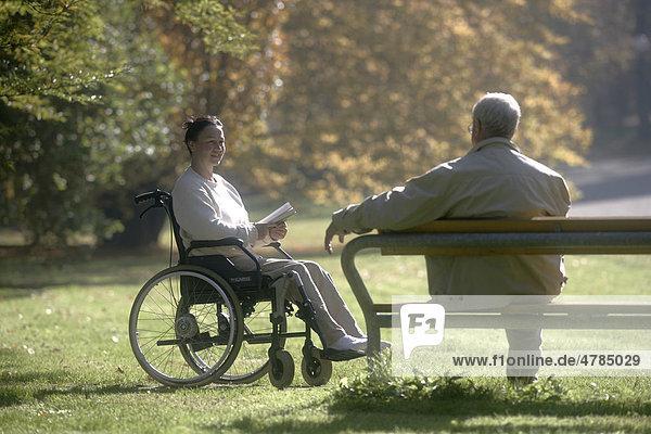 Frau sitzt im Rollstuhl  Mann sitzt auf Parkbank