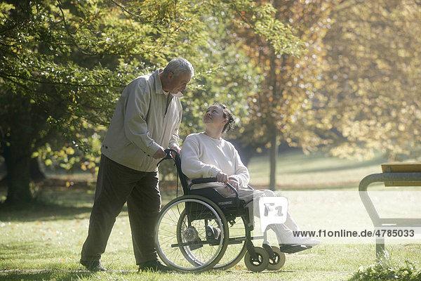 Mann schiebt Frau im Rollstuhl durch Park