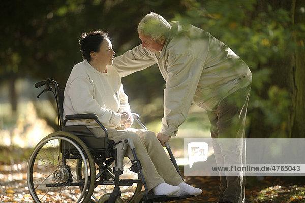 Mann spricht mit Frau im Rollstuhl
