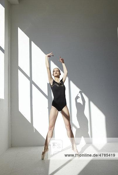 Balletttänzerin mit schwarzem Ballettanzug in weißem Raum